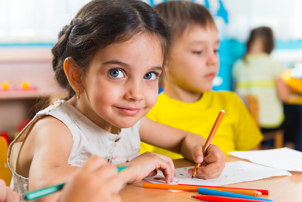 kindergarten girl coloring in a classroom