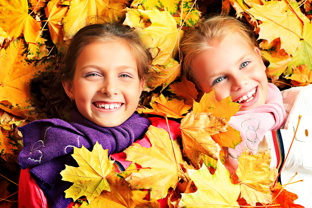 kids in leaves enjoying fall activites