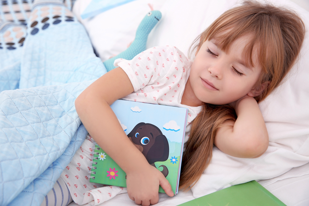 child asleep in bed with a book